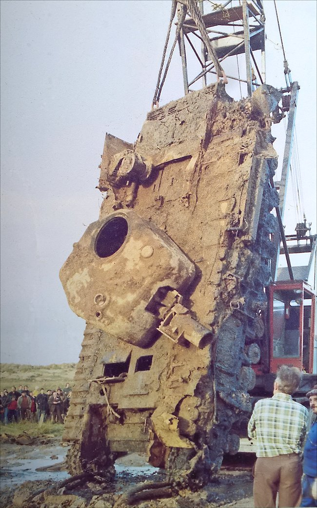 A crain is used to lift the tank out of the mud